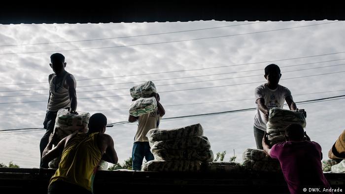 Em Pacaraima, venezuelanos trabalham descarregando caminhão com alimentos que abastecem as lojas da cidade.