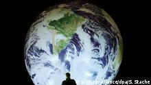 Mann vor Globus Ballon Symbolbild Klimawandel