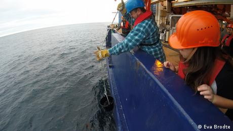 A crew member takes a water sample out of the ocean with a bucket (Eva Brodte)