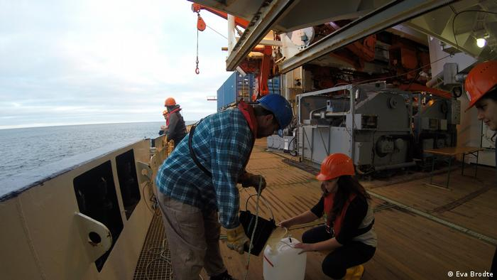 Crew members filling the water sample into a canister (Eva Brodte)