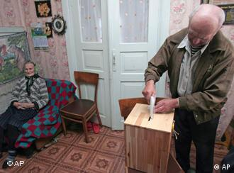 A man casts his ballot hat home as a woman looks on in the background