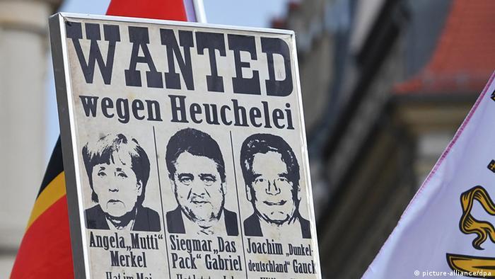 Ein Demoplakat bei Pegida im Stil eines Steckbriefs von Angela Merkel, Sigmar Gabriel und Joachim Gauck (Foto: DPA)