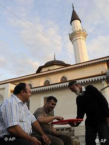 Ein Mann verteilt Süßigkeiten von einer Moschee der Krimtataren in der Krim-Hauptstadt Simferopoll (Foto: AP Photo / Sergei Chuzavkov)