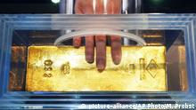 15.12.2016 Fingers are about to touch a 12 kg heavy gold bar with a value of 440 000 euro in the Money Museum in Frankfurt, Germany, Thursday, Dec. 15, 2016. The museum was reopened after two years of renovation.(AP Photo/Michael Probst) |