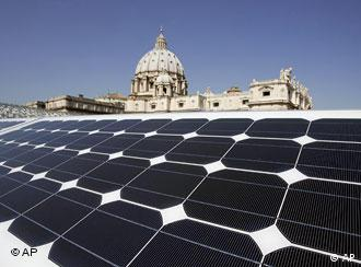 St. Peter's Basilica is seen in the background of a solar panel set up on the roof of the Paul VI Hall