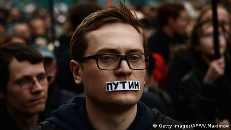 A demonstrator wears a tape over his mouth reading Putin