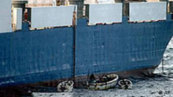 Somali pirates in small boats are seen alongside the hijacked Faina.