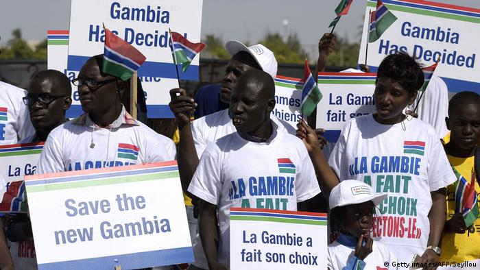 Demonstrators in Gambia's national colors red, blue and green holding posters reading Save the new Gambia and other slogans