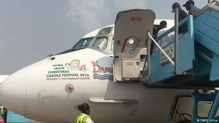 Plane on tarmac bearing advert for Akwa Ibom Christmas Carols Festival