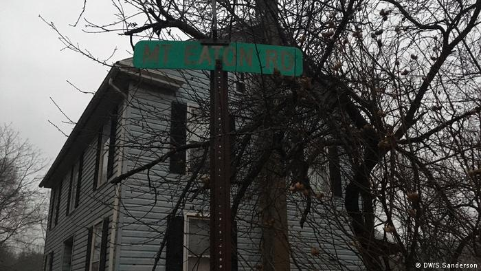 A street sign in front of a house marks Mount Eaton Road