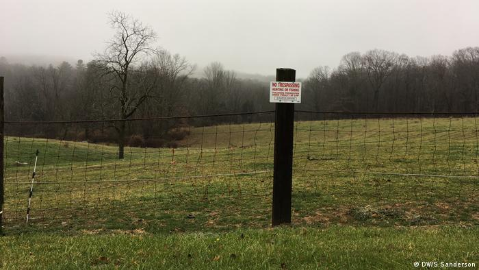 A no trespassing sign on a fence in front of a field