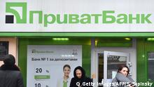 19.12.2016 Clients walk out the office of the PrivatBank in the center of Kiev on December 19, 2016. Ukrainian President Petro Poroshenko urged people on December 19 not to panic after his government nationalised the country's largest private bank to avoid a rapid financial meltdown. The former Soviet republic's cabinet on Sunday took over PrivatBank - a lender that held one-third of Ukrainians' bank deposits and even had branches in the Baltic states. / AFP / Sergei SUPINSKY (Photo credit should read SERGEI SUPINSKY/AFP/Getty Images)