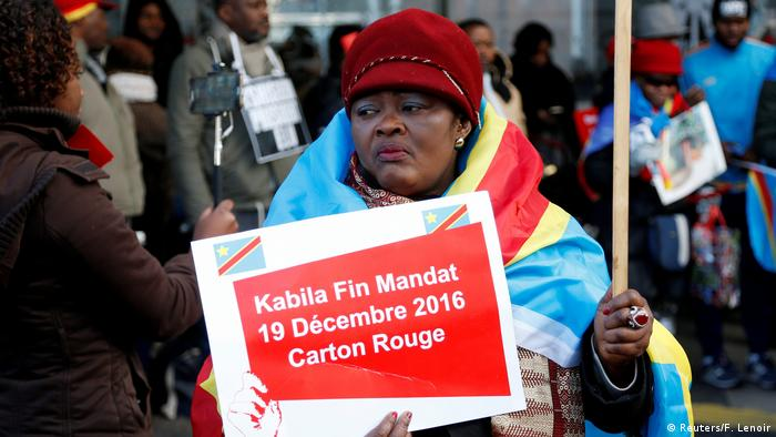 A woman demonstrator holds a sign written in French, which reads 'Kabila end of term - December 19, 2016. Red card'
