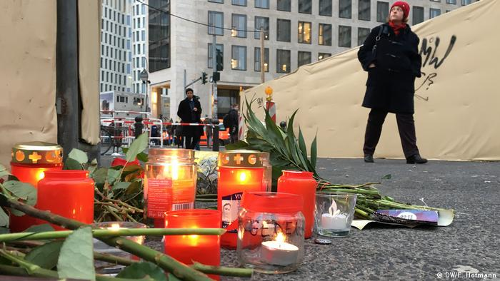 Свечи и цветы у заграждения на площади Брайтшайдплац
