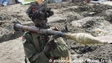 FILE - In this Sunday, Oct. 16, 2016 file photo, a South Sudanese government soldier wearing a wig holds a rocket propelled grenade launcher while standing in a trench in Malakal, South Sudan. The country is on the brink of an all-out ethnic civil war which could destabilize the entire region, the head of a team of U.N. human rights investigators told the U.N. Human Rights Council on Wednesday, Dec. 14, 2016. (AP Photo/Justin Lynch, File)  