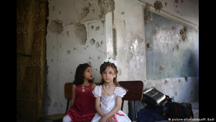 Girls in front of bullet-riddled wall (picture-alliance/dpa/M. Badr)