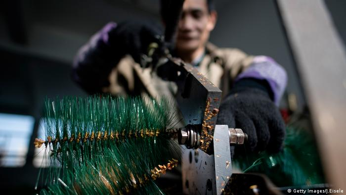 Chinese worker cutting fake branches into pieces in Sun Xudan's artificial Christmas tree factory in Yiwu (Getty Images/J.Eisele)