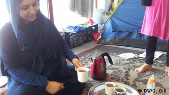 Nadia Saeedi prepares tea in a communal space in Elliko camp