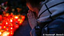 20.12.2016*** A woman prays next to lit candles at the Christmas market in Berlin, Germany, December 20, 2016, where a truck ploughed into the crowd on Monday. REUTERS/Fabrizio Bensch