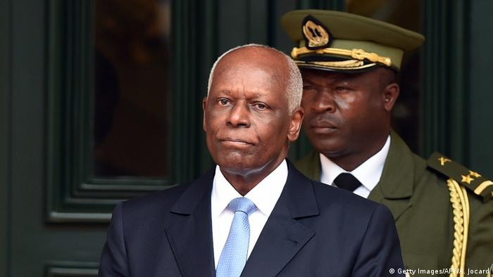 Former Angolan President Jose Eduardo dos Santos, with a soldier standing behind him as he waits for a guest