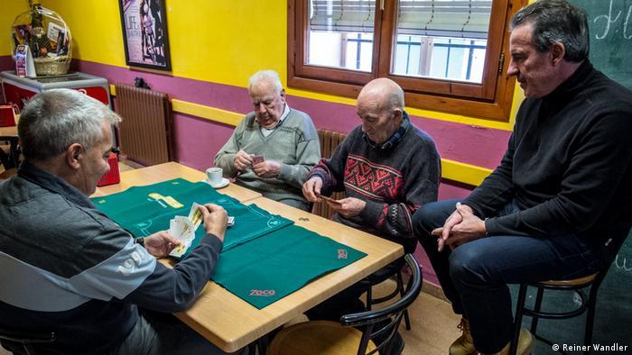 Adultos mayores jugando cartas en una mesa.