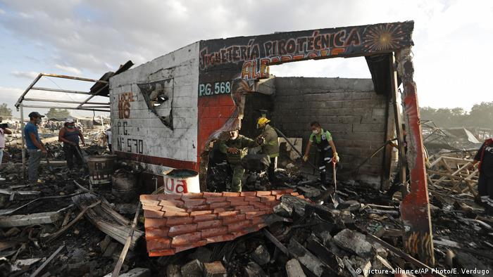 Firefighters and rescue workers walk through the scorched ground of Mexico's best-known fireworks market