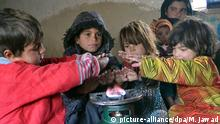 Zia-ul Haq's 4 kids huddled around a burner used as a heater trying to warm themselves in one of the rooms in his small 3-room mud-hut where he lives with a family of 10, including himself, in a small camp in the outskirts of Kabul city on 20 December 2016. He had to flee Kunduz's Chahardara district due to continued fighting where his family was stuck in his house for 13 days. Around 580,000 people have been displaced due to conflict related violence in 2016 alone, surprising the Afghan government and international community alike. Internally Displaced Person (IDP). (zu dpa Vertreibung, Hunger, Kälte - Stille Mörder in Afghanistan vom 21.12.2016) Foto: Mohammad Jawad/dpa +++(c) dpa - Bildfunk+++