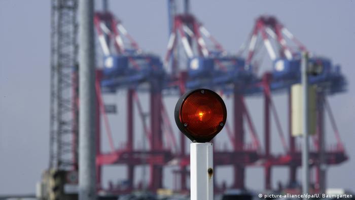 Красный сигнал на фоне кранов в морском торговом порту