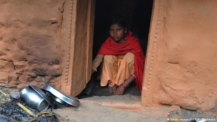 A Nepalese teenager sits inside a hut