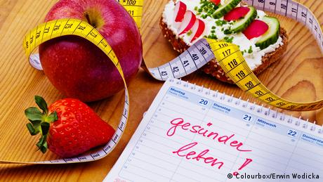 Apple, tape measure, bread with vegetables and a calendar with a good resolution to adopt a healthy lifestyle written on it
