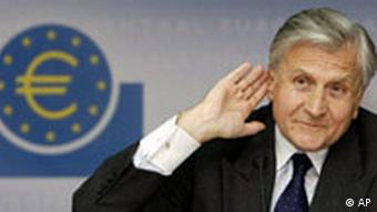 ECB head Jean-Claude Trichet with euro symbol in background and his hand to his ear