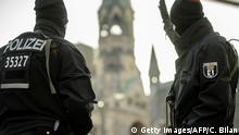 TOPSHOT - Policemen stand guard on December 21, 2016 near the Kaiser-Wilhelm-Gedaechtniskirche (Kaiser Wilhelm Memorial Church) in Berlin, close to the site where a truck crashed into a Christmas market two days before. Twelve people were killed and almost 50 wounded, 18 seriously, when the lorry tore through the crowd on December 19, 2016, smashing wooden stalls and crushing victims, in scenes reminiscent of July's deadly attack in the French Riviera city of Nice. / AFP / CLEMENS BILAN (Photo credit should read CLEMENS BILAN/AFP/Getty Images)