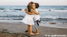 Two kids hugging on a beach (Imago/Westend61)