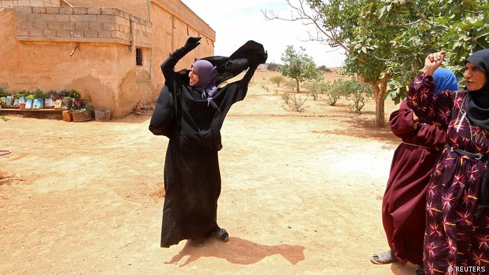 Souad Hamidi removes her Niqab after Syria Democratic Forces took control of her village, on the outskirts of Manbij city, Aleppo province, Syria in June 2016