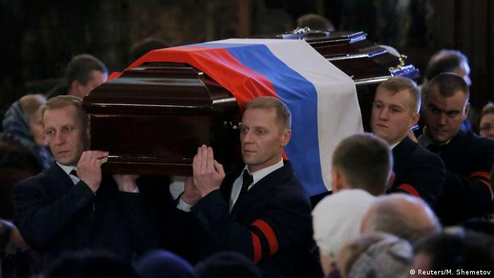 Männer tragen Sarg mit der russischen Flagge