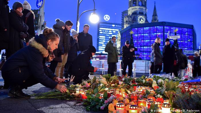 A young woman lights a candle at memorial in Berlin