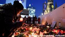 Eine Frau zündet am 21.12.2016 in Berlin unweit der Stelle des Anschlags auf dem Weihnachtsmarkt am Breitscheidplatz Kerzen an. Bei einem Anschlag am 19.12.2016 mit einem Lastwagen auf einen Weihnachtsmarkt an der Gedächtniskirche wurden zwölf Menschen getötet und rund 50 verletzt. Foto: Britta Pedersen/dpa-Zentralbild/dpa   Verwendung weltweit