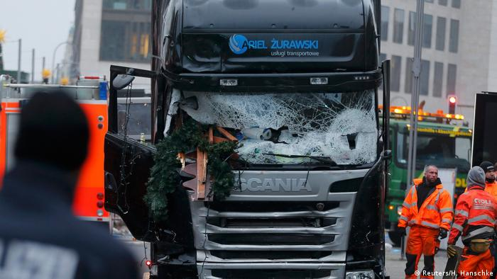 Police stand in front of the truck which ploughed into a crowded Christmas market in the German capital Berlin