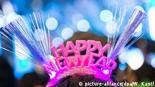Eine Frau trägt am 31.12.2015 bei der Silvesterparty am Brandenburger Tor in Berlin einen Reif mit der Aufschrift HAPPY NEW YEAR. Bei dem Open-Air-Spektakel entlang der Straße des 17. Juni feiern Menschen aus aller Welt den Jahreswechsel. Foto: Wolfram Kastl/dpa +++(c) dpa - Bildfunk+++ |