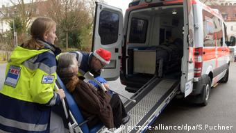 An elderly person is wheeled onto an ambulance