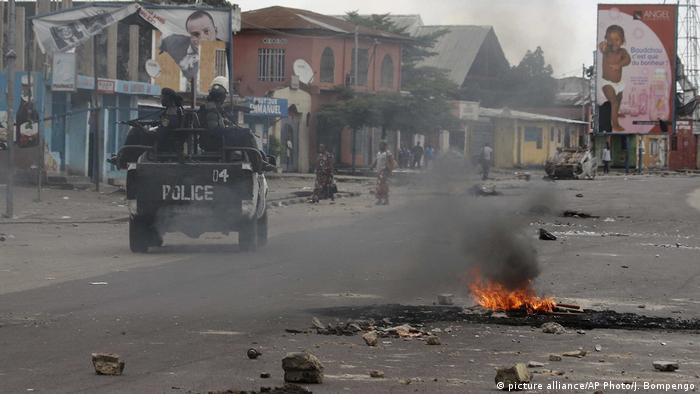 Tyres burning in the streets of Kinshasa as a police can drives by. (picture alliance/AP Photo/J. Bompengo)