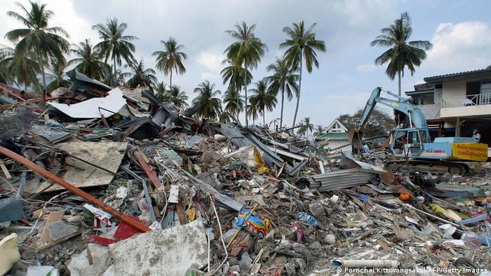 Pilha de destroços e objetos, com coqueiros ao fundo. Uma escavadeira trabalha no local.