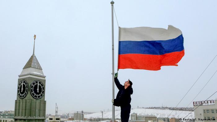 Мужчина приспускает росссийский триколор на флагштоке