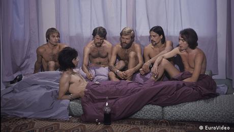 Film Still It Is Not the Homosexual Who Is Perverse, But the Society in Which He Lives, 6 naked men, barely covered, on a mattress. Nicht der Homosexuelle ist pervers, sondern die Situation, in der er lebt (EuroVideo )