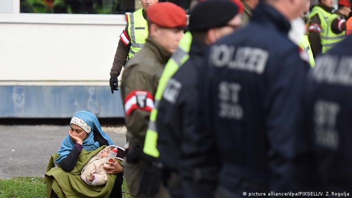 A young migrant woman holds a baby and a bottle while sitting on the grass while police stand to the right of her (picture alliance/dpa/PIXSELL/V. Z. Rogulja)