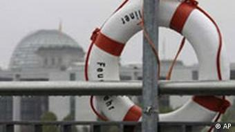 A life buoy sits at the bank of the river Spree in front of the Reichstag, left, in Berlin