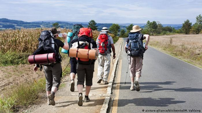 Pilgrims walk down a road with backpacks on their backs (picture-alliance/blickwinkel/M. Vahlsing)