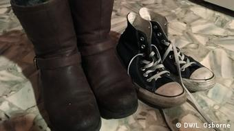 A pair of leather boots next to a pair of black canvas Converse sneakers.