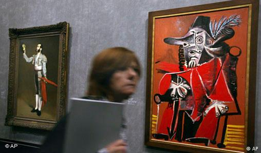 A visitor walks past Pablo Picasso's 1969 oil on canvas Mousquetaire a l'epee assis, right, and Edouard Manet's 1866-1867 oil on canvas Matador saluant exhibited at the Grand Palais museum in Paris, Monday, Oct. 6, 2008. The exhibit matches Picasso paintings alongside the original works that may have inspired them. It cost a total of euros4.3 million (US$5.8 million) to cover fees like insurance and transport for works on loan from other museums, making it one of France's most expensive, and ambitious, exhibits ever. Picasso's masters will be on exhibit from Oct. 8, 2008 until Feb. 2, 2009. (AP Photo/Jacques Brinon)
