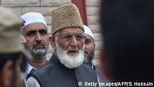 Indian security personnel stand near the chairman of the All Parties Hurriyat Conference (APHC) Syed Ali Geelani (C), who was detained as he tried to march towards army headquarters in Srinagar on August 27, 2016. Police in Indian-administered Kashmir have arrested a top separatist leader, his aide said August 27, as the region's chief minister met Prime Minister Narendra Modi and defended a 50-day lockdown on the region. It came as the number of civilians killed since protests erupted in Kashmir last month after the shooting of a popular militant leader hit 68 August 27, while a police constable was also shot dead. / AFP / SAJJAD HUSSAIN (Photo credit should read SAJJAD HUSSAIN/AFP/Getty Images)